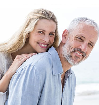 Head and shoulders photo of middle-aged couple smiling at the beach, for information on dental implants from Kentucky Dental Group of Lexington.