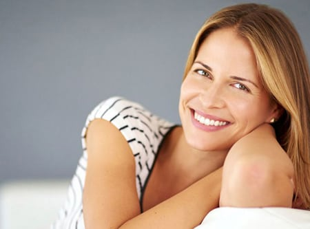Head-and-shoulders photo of a strawberry-blonde woman sitting on a white couch and smiling, for information on Lexington Emergency Dentist from Kentucky Dental Group.