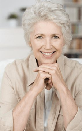 Head-and-shoulders photo of 65+ woman with gray hair sitting on a white couch and smiling with her chin resting on her hands - for information on implant overdentures from Kentucky Dental Group of Lexington.