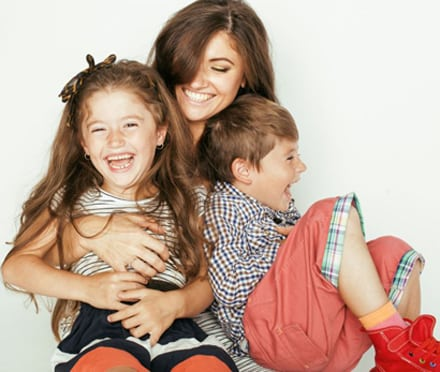 Photo of a brunette mom with long hair playfully holding her daughter and son, for parents looking for a pediatric dentist in Lexington KY.