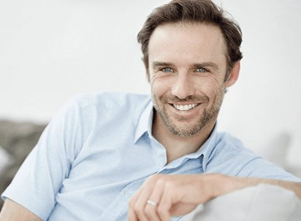 Head-and-shoulder's photo of middle-aged man with a gray-shadow beard. He is wearing a light-blue short-sleeved shirt and sitting on a couch and smiling, for information on porcelain crowns in Lexington, from Kentucky Dental Group.