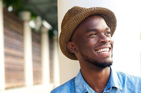 Head-and-shoulders outdoor photo of African American man wearing a hat and smiling, for sedation dentistry from Kentucky Dental Group of Lexington.