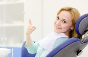 Woman giving thumbs up in a dental chair